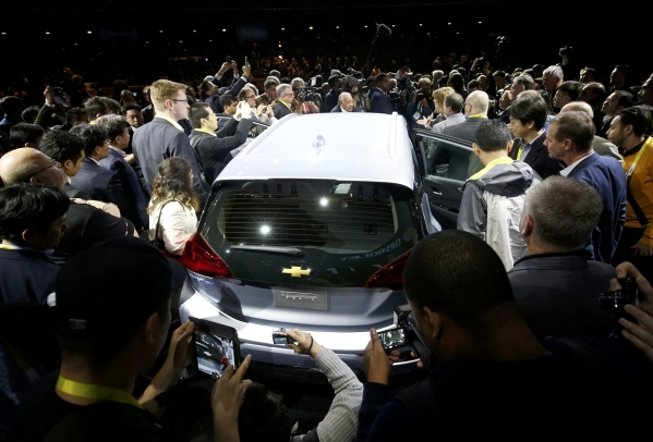 Journalists look over the 2017 Chevrolet Bolt EV after it is unveiled during a General Motors keynote address at the 2016 CES trade show in Las Vegas, Nevada January 6, 2016. The car will have a 2 ...