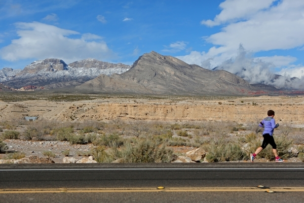 A jogger runs east on state Route 159 near a cloudy and snow-topped Red Rock Canyon National Conservation Area Wednesday, Jan. 6, 2016, near Las Vegas. Ronda Churchill/Las Vegas Review-Journal