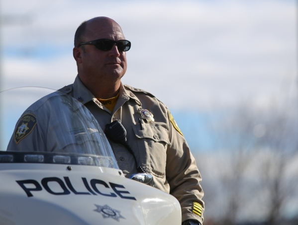 A Metro officer listens to Deputy Chief Gary Schofield makes the announcement to members of the media that Metro will return to responding to non-injury crashes at Las Vegas police headquarters on ...