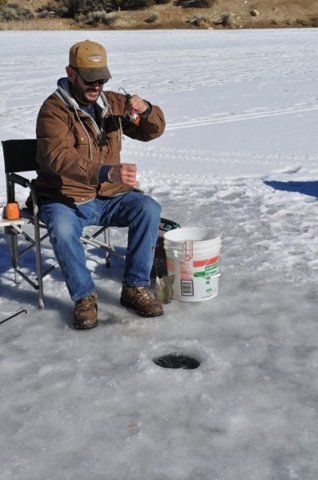 An unidentified fisherman pulls a fish out of a hole on Cave Lake during the annual Ice Fishing Derby sponsored by the Ely Rotary Club. This year's event at the 32-acre Ely reservoir is Jan. ...