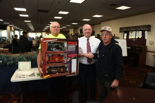 The Las Vegas Garden Railway Society held a Dec. 30, 2015, raffle for a train set. The winner was Tom Neill, far right. At left, club member Rik Edwards holds the trains set nex to Jim Marsh, who  ...