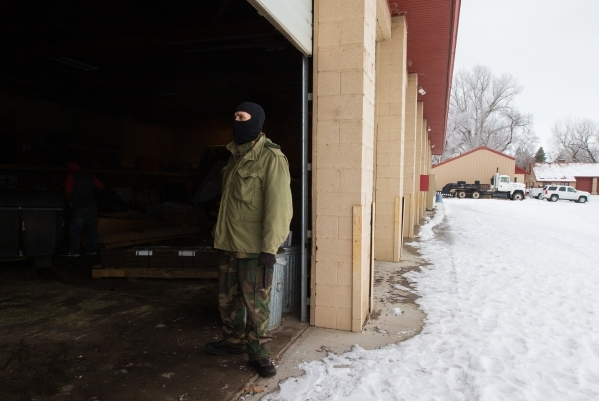 An anti-government protester stands in a garage at the Malheur National Wildlife Refuge headquarters, which the group is occupying, near Burns, Ore. on Thursday, Jan. 7, 2016. The protesters, many ...