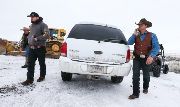 Ryan Bundy right, walks after riding in a U.S. government vehicle to the entrance of Malheur National Wildlife Refuge headquarters near Burns, Ore. on Wednesday, Jan. 6, 2016. Bundy, who, along wi ...