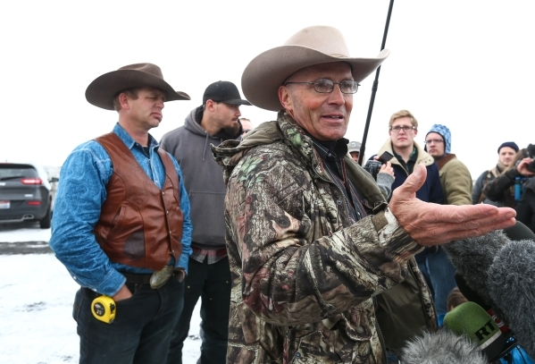 Arizona rancher and anti-government protester LaVoy Finicum, right, talks with reporters as Ryan Bundy, left, looks on, by the entrance of the Malheur National Wildlife Refuge headquarters, which  ...