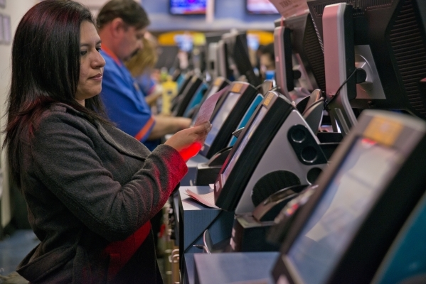 Jenny Rodriguez helps customers purchase lottery tickets inside the Primm Valley Lotto Store just over the California border near Primm on Friday, Jan. 8, 2016. (Daniel Clark/Las Vegas Review-Journal)