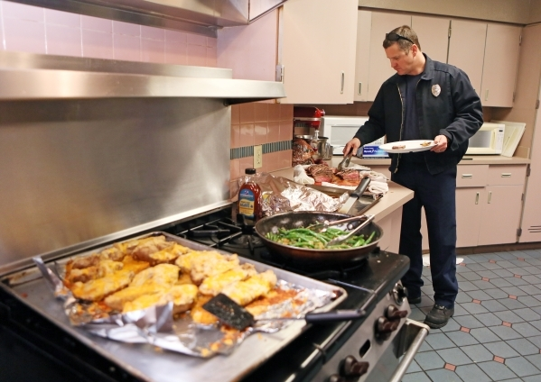 Firefighter Colin Kelley fills a plate with food during a dinner for B Platoon at Clark County Fire Department Station 17 Monday, Jan. 11, 2016, in Las Vegas. Each platoon contributes a daily fee  ...