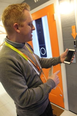 Doug Barnett, an exhibitor with Vivint Smart Home, demonstrates how the system works during CES. When the doorbell rings, people get a text message notification on their phone. (Michael Lyle/Las V ...