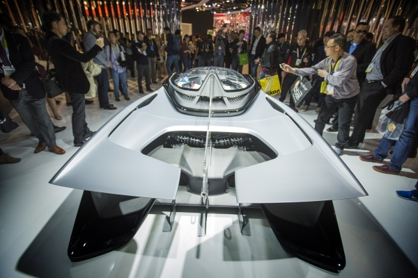 People gather around the FFZero1 concept car at the Faraday Future booth during CES in the Las Vegas Convention Center on Friday, Jan. 8,2016. Faraday Future is schedule to build a manufacturing p ...