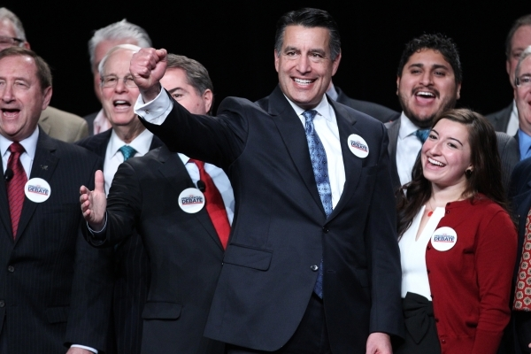 Gov. Brian Sandoval, left, Kanani Espinoza, UNLV student body president, and other special guests pose for photos  during an event to celebrate preparations for the 2016 and final presidential deb ...