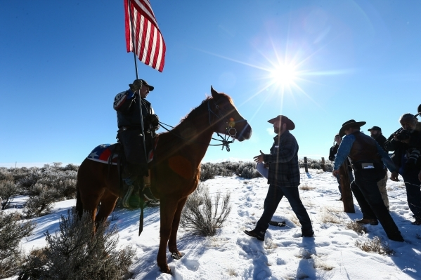 Ammon Bundy, center right, walks up to Duane Ehmer, of Irrigon, Ore., after a news conference by the entrance of Malheur National Wildlife Refuge headquarters near Burns, Ore. on Friday, Jan. 8, 2 ...