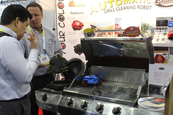 Ethan Woods shows a CES visitor how the Grillbot works to clean a grill..(Michael Lyle/Las Vegas Review-Journal)