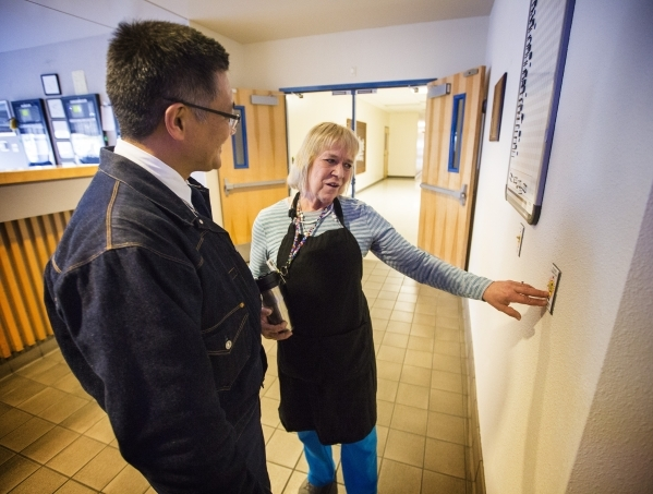 Employee Cheryl Smith explains to Michael Kobori, VP of sustainability for  Levi Strauss & Company, at light switch plate she created at the Levi Strauss & Company's Sky Harbor Distr ...