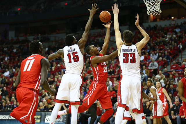 UNLV forwards Stephen Zimmerman Jr. (33) and Dwayne Morgan (15) defend as New Mexico guard Sam Logwood (20) attempts a shot, which was blocked by Zimmerman, during a basketball game at the Thomas  ...
