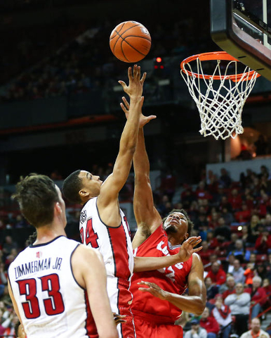 UNLV guard Jalen Poyser (24) sends in a shot at the basket over New Mexico forward Tim Williams (32) during a basketball game at the Thomas & Mack Center in Las Vegas on Tuesday, Jan. 12, 2016 ...