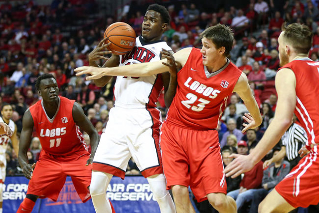 UNLV forward Dwayne Morgan (15) tries to pull in a rebound against New Mexico forward Joe Furstinger (23) as New Mexico center Obij Aget (11) looks on during a basketball game at the Thomas &  ...