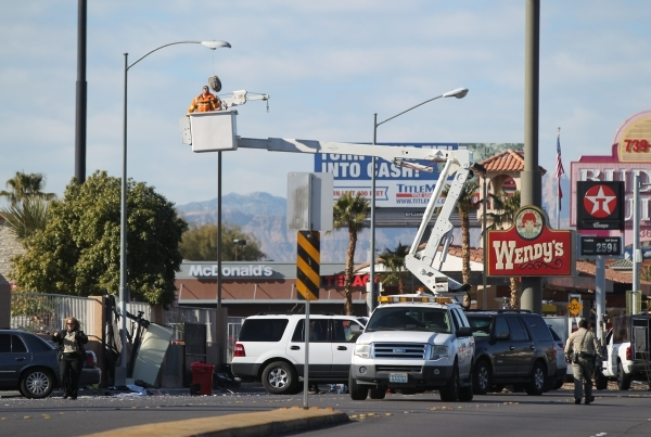 A utility worker takes down a street light that was damaged as part of a fatal accident where a bus hit a bus stop on West Tropicana Avenue near Dean Martin Drive in Las Vegas on Saturday, Jan. 9, ...