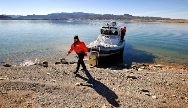 National Park Service ranger Nate Snyder walks on a beach after docking his vessel on a island during the annual eagle count at Lake Mead on Tuesday, Jan. 12, 2016. National Park Service and other ...