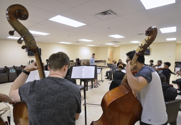 Bass players Daniel Skurski, left, and Joshua Riel perform as Yunior Lopez, center background, conducts during a Young Artists Orchestra rehearsal at the Adelson Clinic at 3661 Maryland Parkway in ...