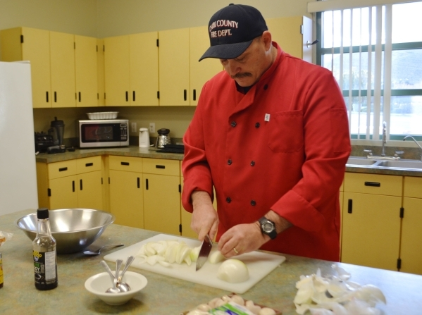 Aaron Smith chops onions at Clark County Fire Department Station 65 Jan. 8. Smith said he's heard plenty of advice on how to keep from crying while cutting onions from holding a piece of bre ...