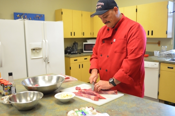 Aaron Smith slices tri-tip steak to make Mongolian beef at Clark County Fire Department Station 65 Jan. 8. Ginger Meurer/Special to View