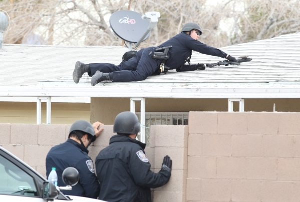 A North Las Vegas police officer positions himself on the roof of a house at the 2600 block of St. George Street, near Carey Avenue and Civic Center where a man was making threats and locked himse ...