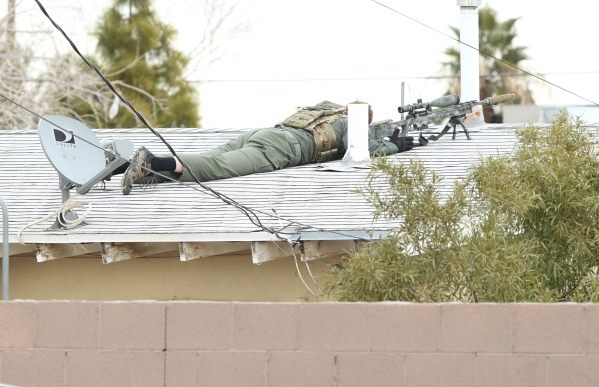 Member of a SWAT team positions himself on the roof of a house at at the 2600 block of St. George Street, near Carey Avenue and Civic Center where a man was making threats and locked himself insid ...