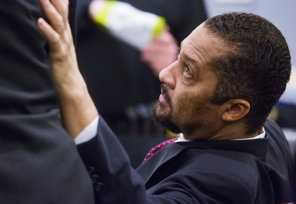 Otis Holland, a former pastor accused of sexually assaulting young girls, touches his attorney before testifying in his own defense at Regional Justice Center, 200 Lewis Ave., in Las Vegas on Wedn ...