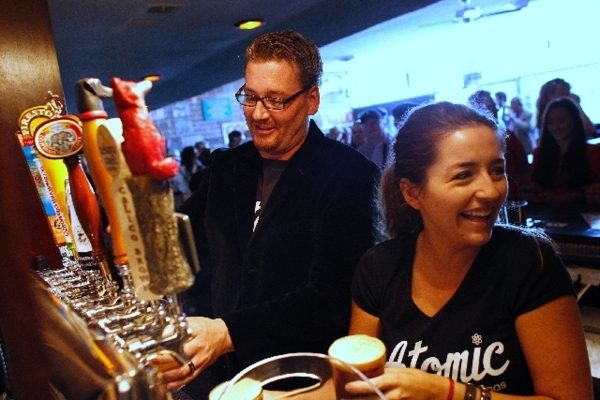 Owner Derek Stonebarger, left, and bartender Ashlea Latham pour beers during the opening of Atomic Liquors in June 2013 in downtown Las Vegas.