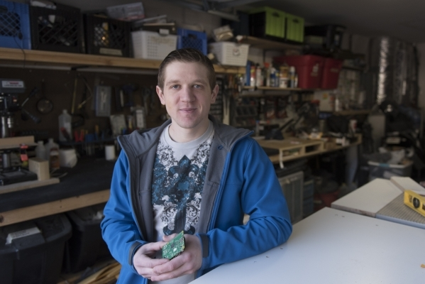 Kyle Kimsey poses with a Raspberry Pi 2 chip that he plans to desolder and install into one of his drones in his workspace at his Las Vegas home Thursday, Jan. 14, 2016. Kimsey is the winner of th ...