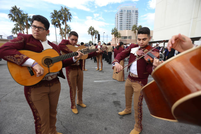 Carlos Fernandez, left, Jeyson Estrada, and Markos Valerio of Mariachi Los Dorados, practice while they wait for the Martin Luther King Jr. Parade to start in Downtown Las Vegas Monday, Jan. 18, 2 ...