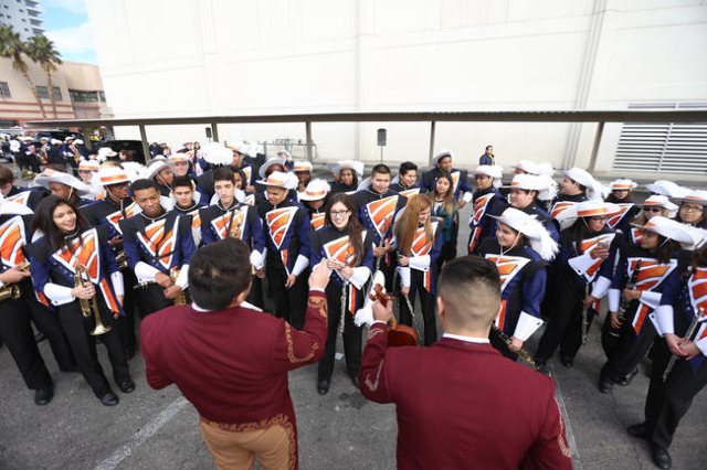 Mariachi Los Dorados plays a song by request of a member from the Legacy High School marching band while they wait for the Martin Luther King Jr. Parade to start in Downtown Las Vegas Monday, Jan. ...
