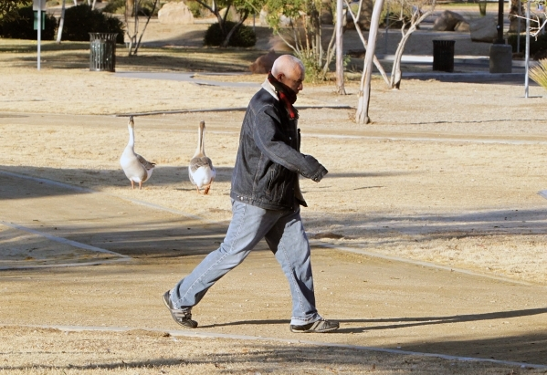 A man, who did not wish to give his name, walks near the Sun Set Park pond during a warm morning, on Thursday, Jan. 14, 2016, in Las Vegas. Sunny skies and normal temperatures are expected to stic ...