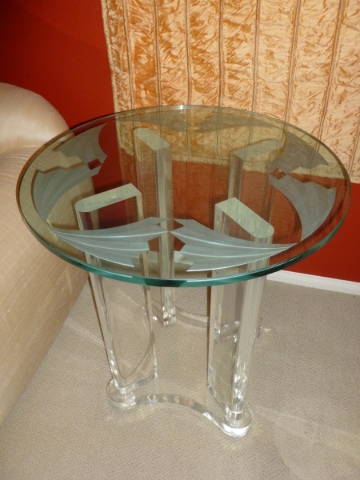 The clear acrylic base features a carved design on three-quarters-inch clear glass top. COURTESY OF SOLEIL DESIGN