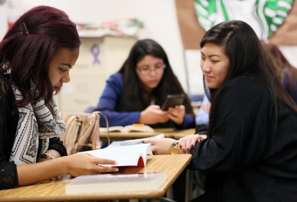 Deja McClellan, left, and Issabella Chang (cq), right, look at a book during a senior´s Teach Academy class supervised by Luanne Wagner at Clark High School Friday, Jan. 15, 2016, in Las Vegas. ...