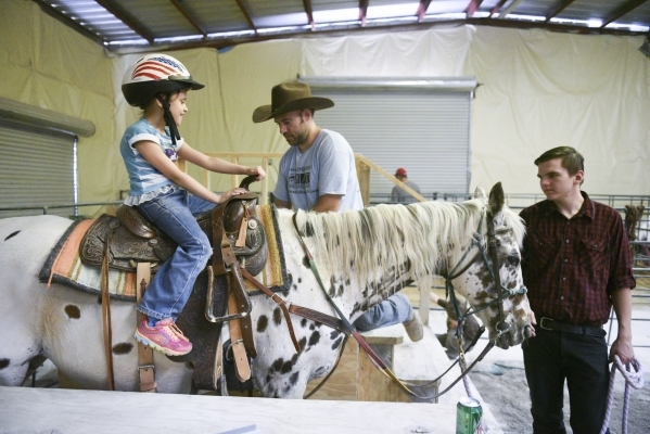 From left, Sophia Nola Hudig, 7, Paul Rogers, owner of Paradise Ranch, and Chris Bratthen, Paul's son, get the horse Pocahontas ready for a ride at Paradise Ranch in Las Vegas, Wednesday, Ju ...