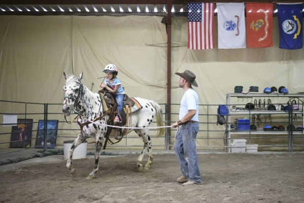 Horse Assisted Therapy (HAT) participant, Sophia Nola Hudig, 7, left, and Paul Rogers, owner of Paradise Ranch in Las Vegas, take Pocahontas for a trot, Wednesday, June 3, 2015. Hudig, who has bee ...