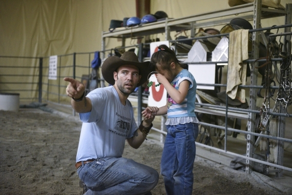 Horse Assisted Therapy (HAT) program participant Sophia Nola Hudig, right, struggles to follow Paul Roger's instruction to put an item away at Paradise Ranch in Las Vegas, Wednesday, June 3, ...