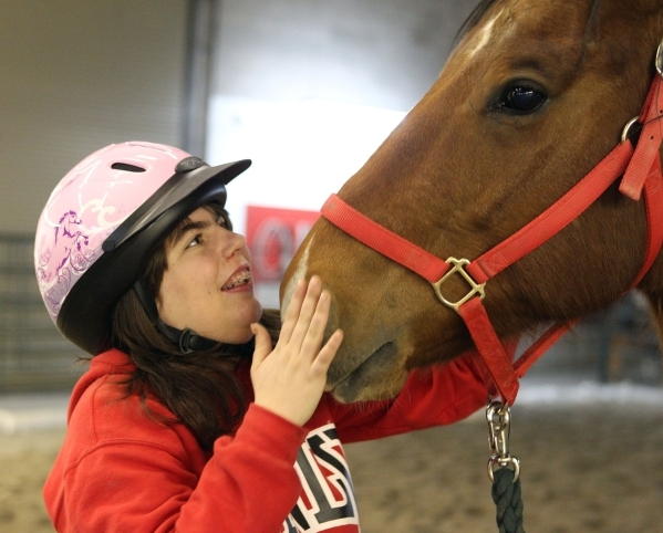 Erin McCollom, 17, pets Leo's nose before her ride at Paradise Ranch in Las Vegas, Friday, March 2, 2012. Paradise Ranch offers therapeutic horse back riding to children with autism and othe ...