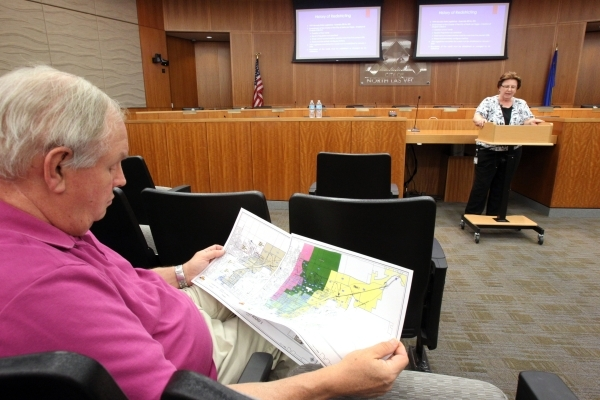 A North Las Vegas resident who declined to give his name, left, checks out maps during a presentation from City Clerk Barbara Andolina at a town hall meeting on the city's proposed redistric ...