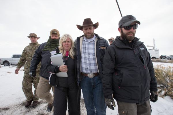Ammon Bundy, center right, with Shawna Cox, walks with supporters after speaking with reporters at a news conference by the entrance of Malheur National Wildlife Refuge near Burns, Ore. on Monday, ...
