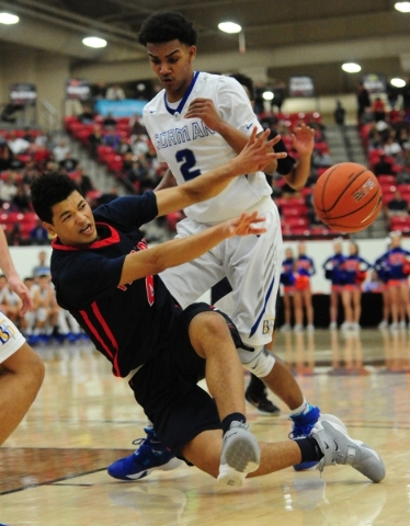 Findlay Prep guard Skylar Mays (4) passes while falling in front of Bishop Gorman guard Jamal Bey (2) in the fourth quarter of their prep basketball game at the South Point Arena in Las Vegas Satu ...