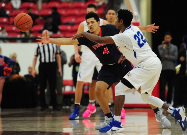 Bishop Gorman guard Christian Popoola passes in front of Findlay Prep guard Skylar Mays (4) in the fourth quarter of their prep basketball game at the South Point Arena in Las Vegas Saturday, Jan. ...