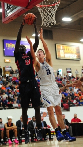 Findlay Prep guard Lamine Diane (24) grabs a defensive rebound against Bishop Gorman forward Zach Collins (12) in the second quarter of their prep basketball game at the South Point Arena in Las V ...