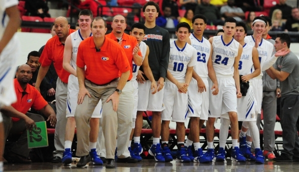 Bishop Gorman head coach Grant Rice, middle left, and players look on in the closing minutes of the second quarter of their prep basketball game at the South Point Arena in Las Vegas Saturday, Jan ...