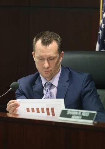 Gaming Control Board chairman A.G. Burnett looks over paperwork provided by Station Casinos during a hearing at Grant Sawyer building Thursday, Jan. 21, 2016, in Las Vegas. The board signed off on ...