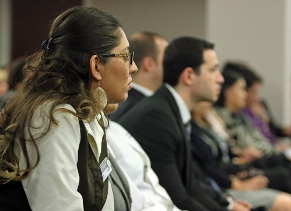 Boulder Station employee Yesenia Quintana, left, sits in a crowded room an attends a Gaming Control Board hearing at Grant Sawyer building Thursday, Jan. 21, 2016, in Las Vegas. The board signed o ...