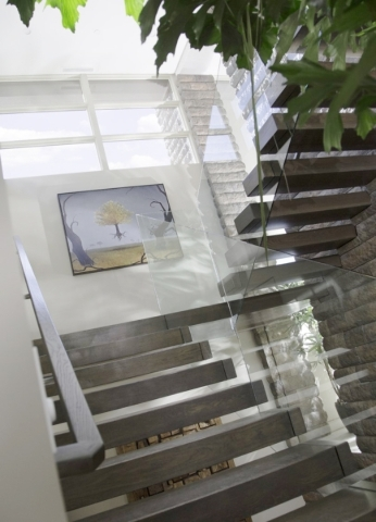 A floating stairway leads back down to the second and first floors. No stair supports are visible under each of the wooden stair steps attached the side of each wall as a visitor winds down four f ...