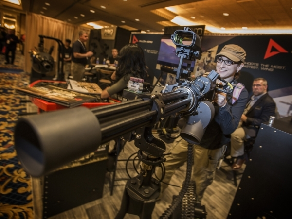 Sarah Caito poises for a photo beside a Dillion mini gun during the Shot Show at the Sands Expo on Tuesday, Jan. 19, 2016. The gun can shoot 3,000 rounds a minute. Jeff Scheid/Las Vegas Review-Jou ...