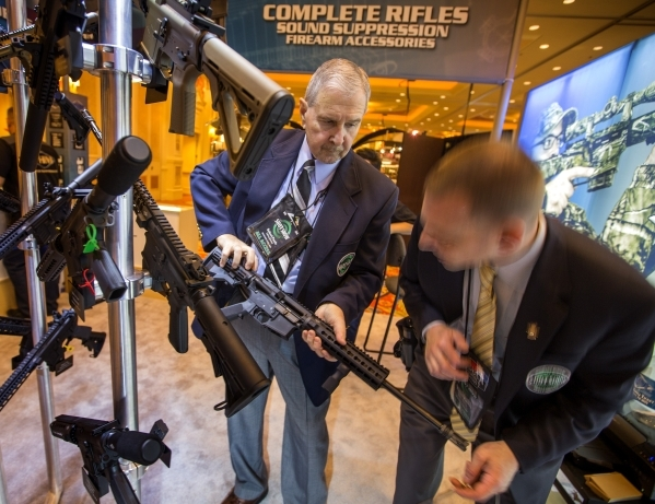 Security personal Robert Poole, left, and Russell Karster, inspects the firing mechanism on a rifle at the Yankee Hill Machine booth during the Shot Show at the Sands Expo on Tuesday, Jan. 19, 201 ...
