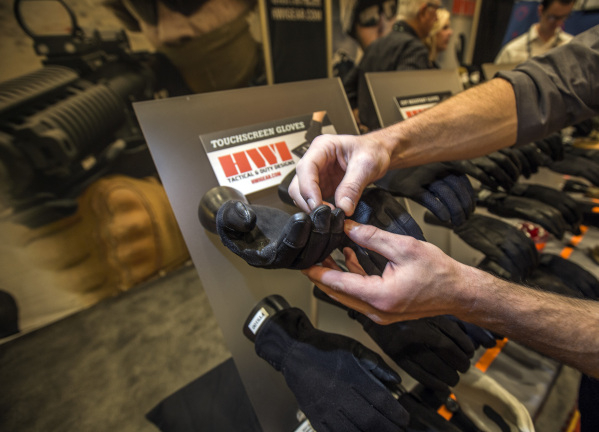 Isaac Hatch with HWI Gear touches gloves that can be used on touchscreen devices during the Shot Show at the Sands Expo on Tuesday, Jan. 19, 2016. Jeff Scheid/Las Vegas Review-Journal Follow @jlscheid